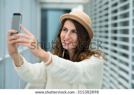 Pretty young woman in fedora smiling and taking selfie
