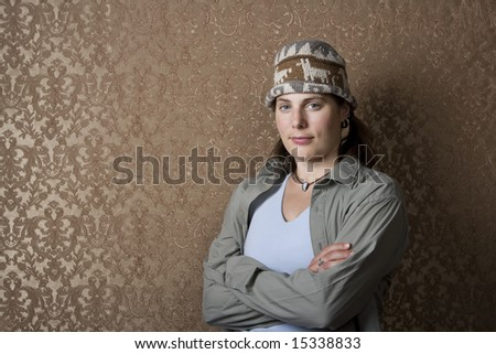Pretty young woman in front of gold wallpaper - stock photo