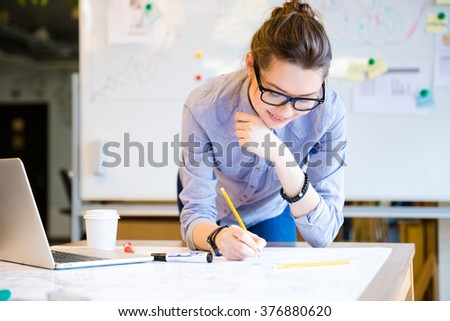 Pretty young woman in glasses using laptop and drawing blueprint by pencil in the office - stock photo