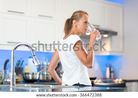 Pretty, young woman in her modern, clean and bright kitchen, pouring herself and drinking a glass of cold tap water(color toned imagey; shallow DOF) - stock photo