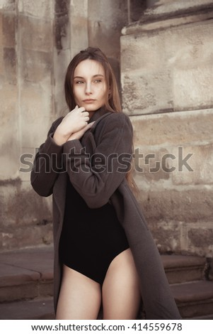Pretty young woman in lingerie and grey coat - stock photo