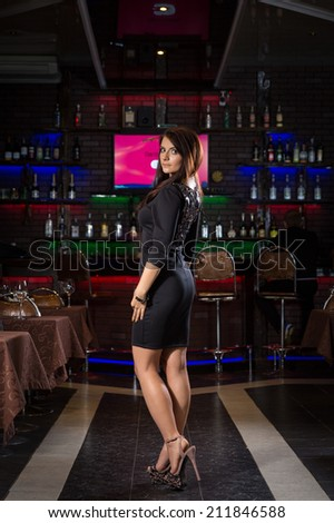 pretty young woman in nightclub standing alone - stock photo