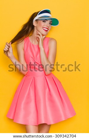 Pretty young woman in pink dress and sun visor holding her hair and posing against yellow background. - stock photo