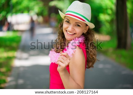 Pretty young woman in pink dress at green summer park