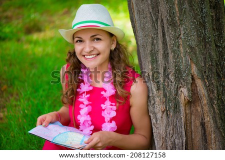 Pretty young woman in pink dress with map at green summer park - stock photo