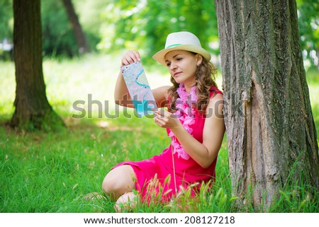 Pretty young woman in pink dress with map at green summer park