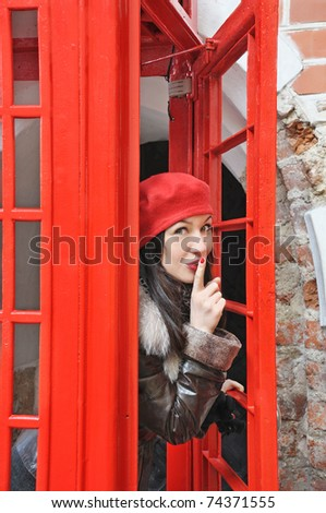 pretty young woman in red hat look out from phonebox - stock photo