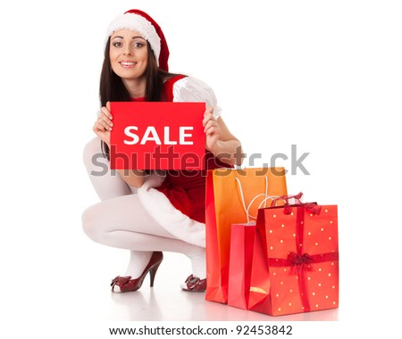Pretty young woman in Santa's suit with shopping bags on a white background.