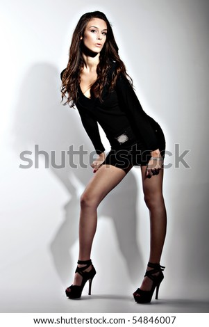 pretty young woman in short black dress on high heels, studio shot