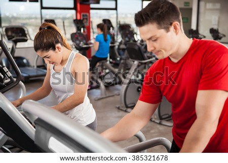 Pretty young woman in sporty outfit choosing a running program on a treadmill next to a guy at the gym - stock photo