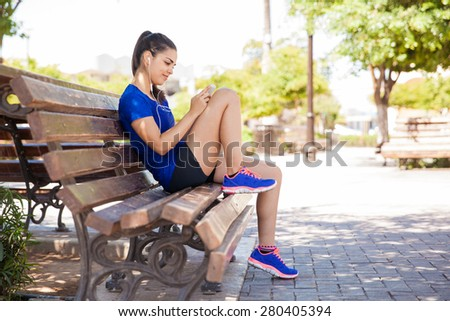 Pretty young woman in sporty outfit using a smartphone and listening to music while sitting on a park bench - stock photo