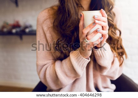 Pretty young woman in stylish pink sweater holding coffee or cappuccino in hands. Warm soft cozy image. Details. - stock photo