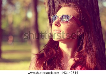 Pretty young woman in sunglasses on the natural background - stock photo