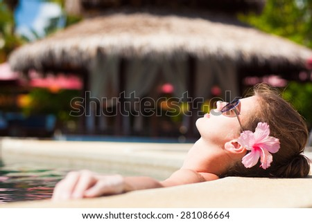pretty young woman in sunglasses with flower in hair in luxury pool - stock photo
