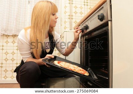 pretty young woman in the kitchen prepares a pizza, adjusts the oven and puts the pizza in - stock photo