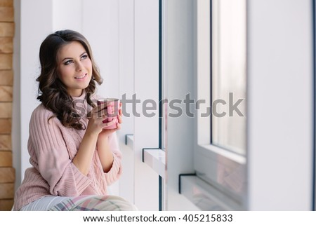 Pretty young woman in the pink sweater sitting nestled plaid and drinking coffee on the windowsill near the window