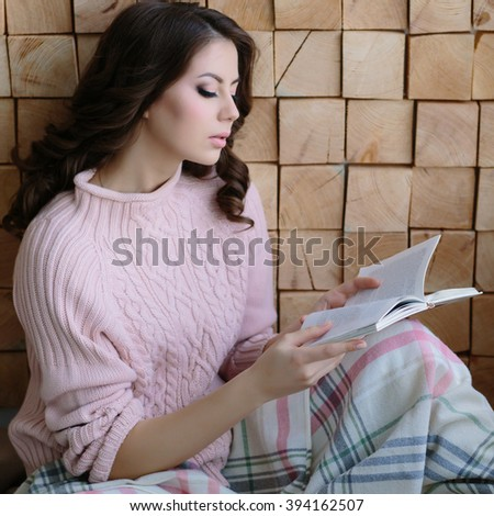 Pretty young woman in the pink sweater sitting nestled plaid and reading the book
