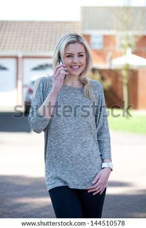 Pretty young woman in UK using mobile phone
