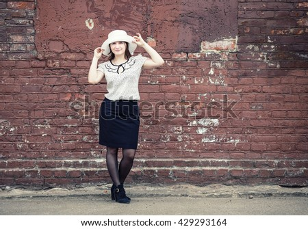 Pretty young woman in white hat, blouse and black skirt, standing against brick wall background. Girl holds the edges of the hat by hands. Toned photo with copy space. Vintage style photo. - stock photo