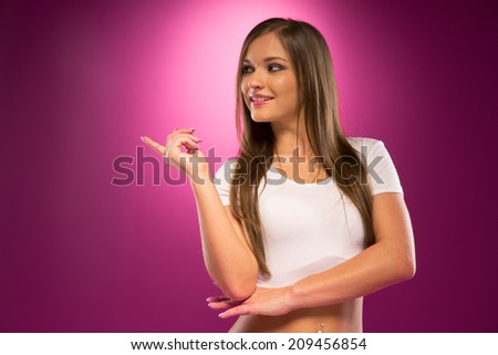 Pretty Young Woman in White Shirt Pointing Something to the Right.Isolated on Violet Background - stock photo