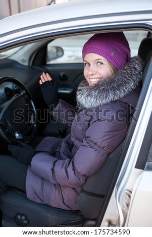Pretty young woman in winter clothes sitting in a car - stock photo