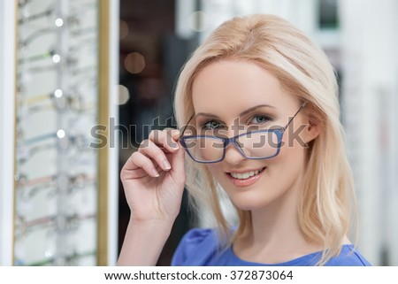 Pretty young woman is choosing new glasses - stock photo