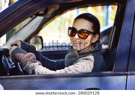 pretty young woman is driving a car - stock photo