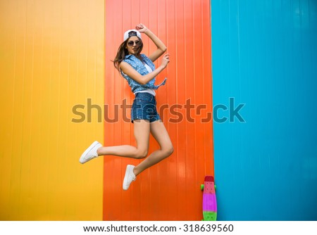Pretty young woman is jumping with against the colorful wall. - stock photo
