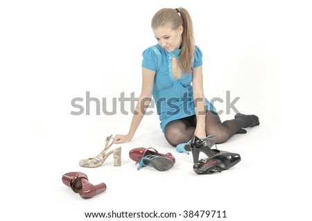 Pretty young woman is lying over white and choosing shoes