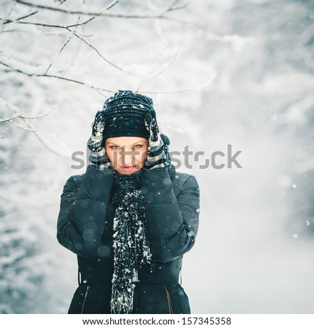 Pretty Young Woman Is Protecting Herself from Snowfall - stock photo