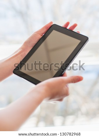 Pretty young woman is using a Tablet PC - stock photo