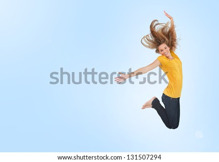 Pretty young woman jumping for joy on blue background - stock photo