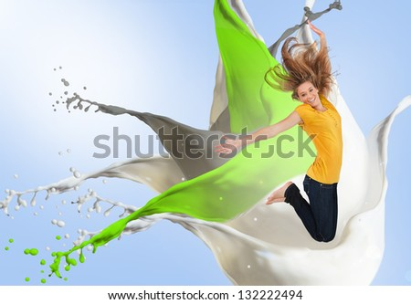 Pretty young woman jumping for joy with artistic green white and grey paint splashes on blue background - stock photo