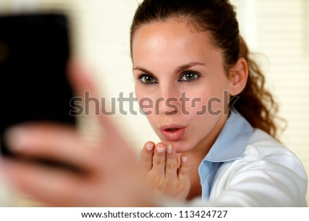 Pretty young woman kissing to cellphone at soft colors composition