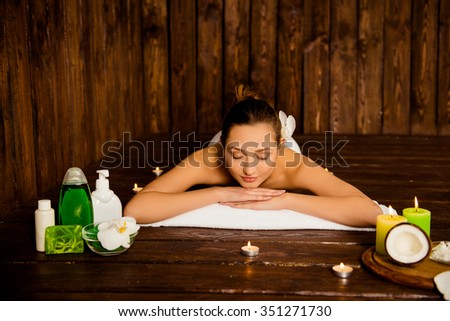 Pretty young woman laying in spa salon with closed eyes and relaxed - stock photo