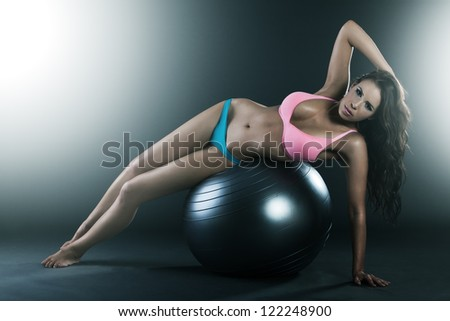 Pretty young woman laying on fit ball, doing workout, smiling - stock photo