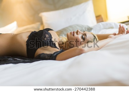 Pretty young woman laying on the bed - stock photo