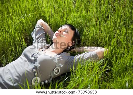 Pretty young woman lie on green grass