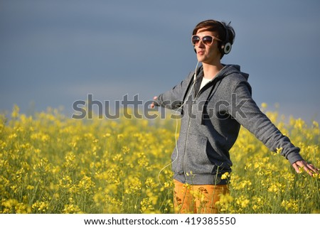 Pretty young woman listening to music in earphones in the outdoors
