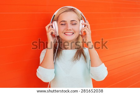 Pretty young woman listens and enjoys the music in headphones against the colorful orange wall - stock photo
