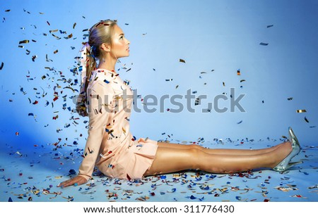 Pretty young woman look like a doll is sitting under bright confetti over blue background. - stock photo
