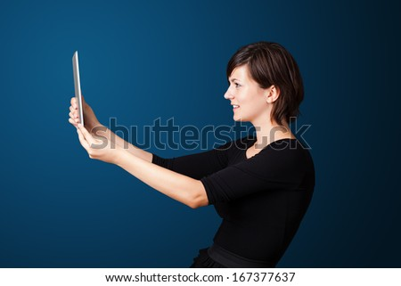Pretty young woman looking at modern tablet
