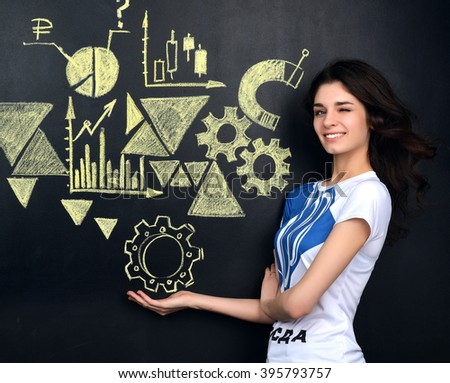 Pretty young woman looking at stock market graphs and symbols on school board winking background