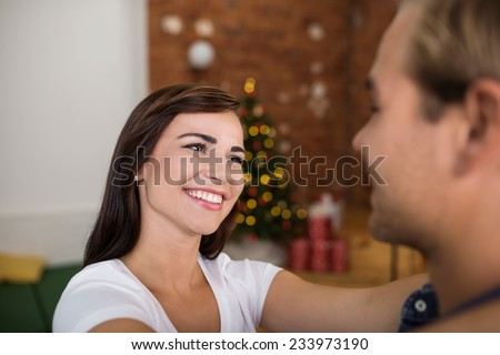 Pretty young woman looking lovingly at her husband smiling into his eyes as she stands with her hands around his neck - stock photo