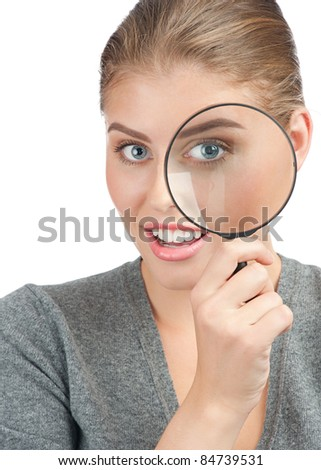 Pretty young woman looking through a magnifying glass. Isolated on white background - stock photo