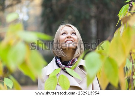 Pretty young woman looking upwards in a forest