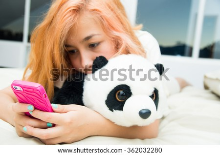 Pretty young woman lying comfortably on bed hugging stuffed panda animal and using pink mobile phone with large windows background. - stock photo