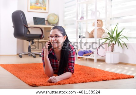Pretty young woman lying on carpet in the room and talking on cell phone - stock photo