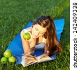pretty young woman lying on green grass reading book with green apples - stock photo