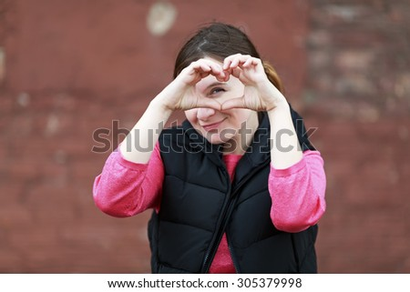 Pretty young woman making a heart gesture with her hands. Girl shows the heart with his hands. Shallow depth of field. Selective focus on the model's face. - stock photo